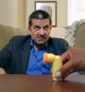 A man frowns as a hand puts a metered dose inhaler on the table in front of him.
