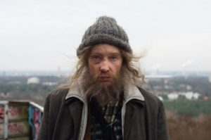Actress Cate Blanchett in the disguise of a bearded homeless man
