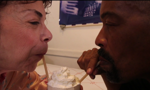 A man and a woman drinking from the same ice cream soda with straws