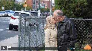 An older couple standing on the sidewalk, kissing.