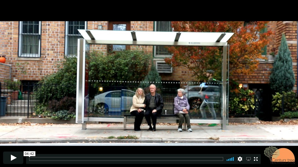 An older couple sitting on the bench of a city bus shelter