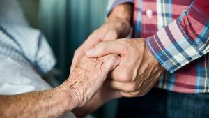 A close up of a man's hands holding an older woman's hand.